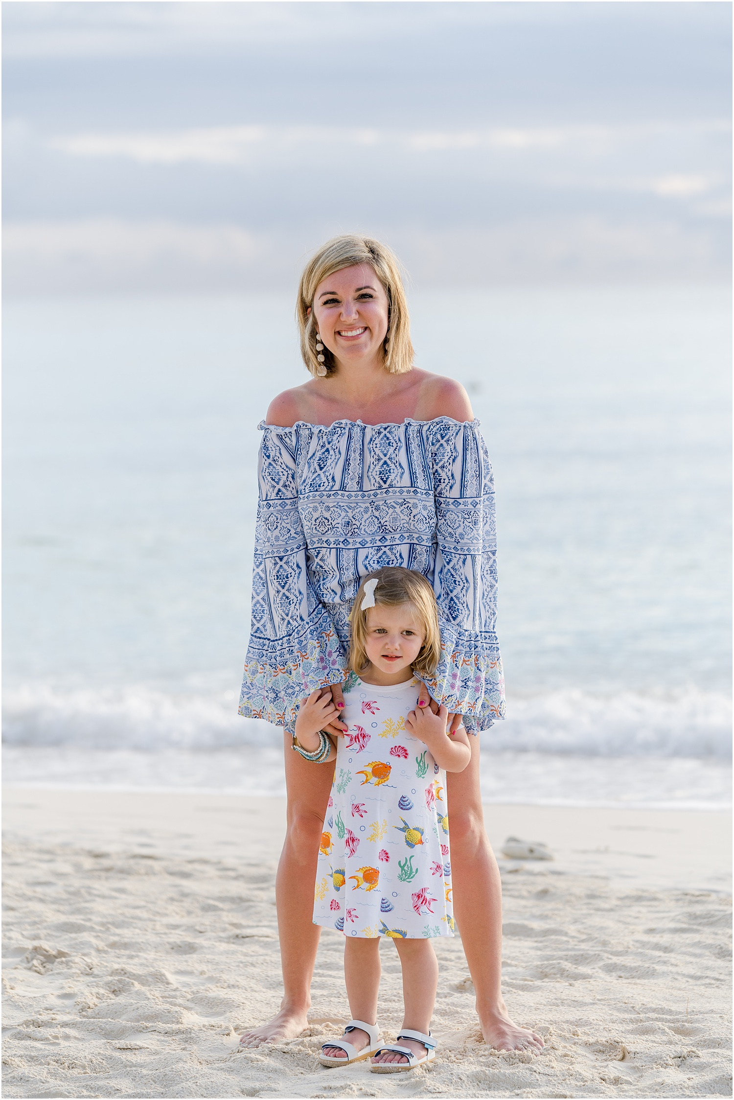 Mom, and daughter on beach. Blue and white outfits.